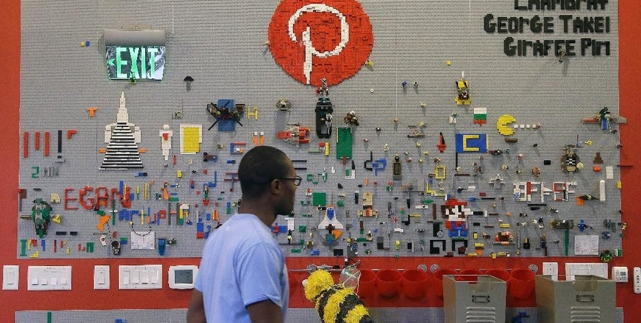 In this Nov. 13, 2014 photo, a Pinterest employee walks past the Lego wall at the Pinterest office in San Francisco. The San Francisco-based venture capital darling celebrated its fifth birthday in March 2015. (AP Photo/Jeff Chiu)