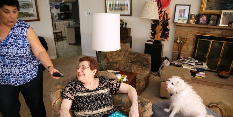 """In this photo taken April 3, 2015, Eleanor Blum, 88, sits with with her dog """"Cutie"""" to continue solving her daily crossword puzzles, as her daughter, Jeri Vargas brings her over the wireless phone at their home in the Sherman Oaks area of Los Angeles. Jeri Vargas put her elderly mother on the """"Do Not Call"""" list years ago. So why is the 88-year-old woman with Alzheimer's disease still getting several recorded phone calls a day pitching her everything from vacation cruises to medical alert devices and fire extinguishers?  (AP Photo/Damian Dovarganes)"""