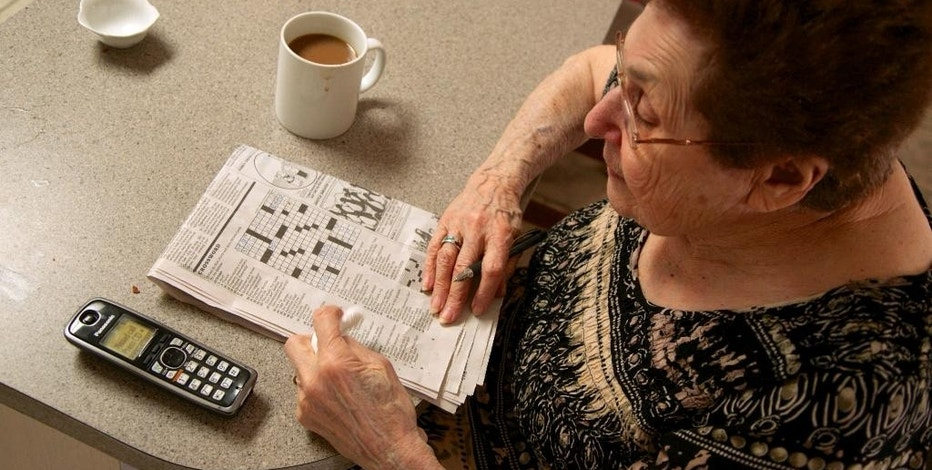 """In this photo taken April 3, 2015, Eleanor Blum, 88, solves crossword puzzles with her wireless phone next to her in the Sherman Oaks area of Los Angeles. Jeri Vargas put her elderly mother on the """"Do Not Call"""" list years ago. So why is the 88-year-old woman with Alzheimer's disease still getting several recorded phone calls a day pitching her everything from vacation cruises to medical alert devices and fire extinguishers? (AP Photo/Damian Dovarganes)"""
