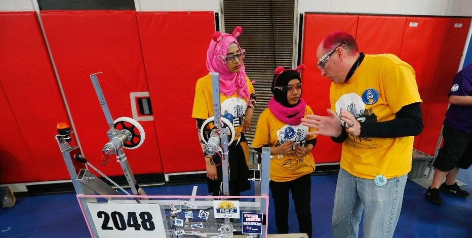 In this March 27, 2015 photo, Detroit International Academy for Young Women students Tunzzina Chowdhury, left, and Papia Aziz listen to Dennis Cabay, right, a team mentor, talks about their robot during the For Inspiration and Recognition of Science and Technology, FIRST, Robotics district competition in Livonia, Mich. Michigan has more high school teams competing in the annual contest than any other state. (AP Photo/Paul Sancya)