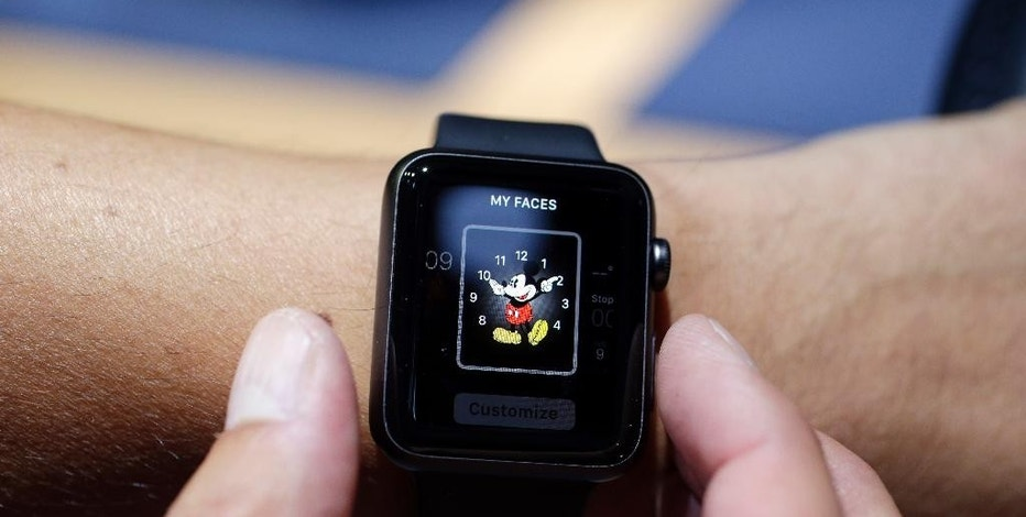 FILE - In this Sept. 9 2014 file photo, an Apple Watch featuring a Mickey Mouse face is tried out during an event in Cupertino, Calif. Apple Watch, available for pre-order on Friday, April 10, 2015, comes with a choice of watch case, band and size _ there are 54 possible configurations in all. (AP Photo/Marcio Jose Sanchez, File)