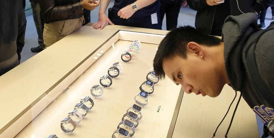 A customer looks at a line of Apple's new watches displayed at a store in San Francisco, Friday, April 10, 2015. Apple has started taking orders for the watch on its website and the Apple Store app. Currently, that's the only way Apple is selling the watch, with shipments scheduled to start April 24. (AP Photo/Eric Risberg)
