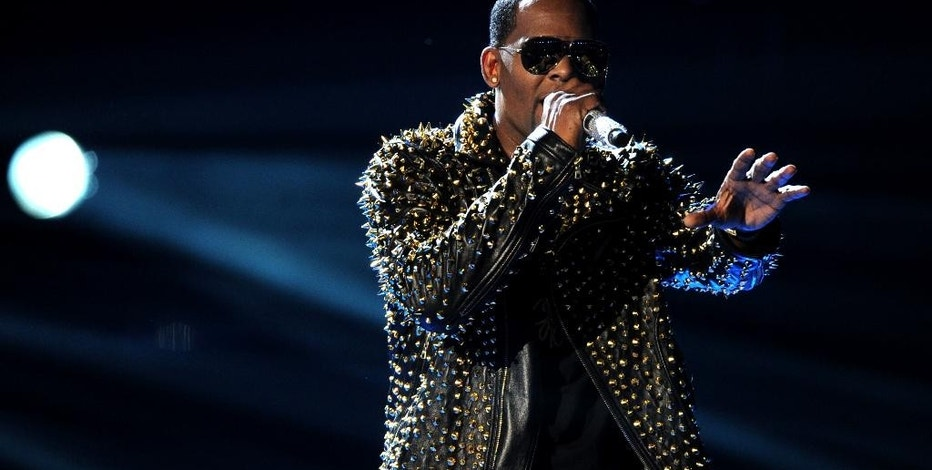 FILE - In this June 30, 2013 file photo, R. Kelly performs onstage at the BET Awards at the Nokia Theatre  in Los Angeles. The owners of 5001 Flavors knew when they started the company 23 years ago they wanted to sell custom-made clothes to rap and R&B musicians. They sought out artists and record company executives at parties and music industry events. They looked in particular for up-and-coming artists. Now musicians like R. Kelly and Kid Rock are among their fans. (Photo by Frank Micelotta/Invision/AP)