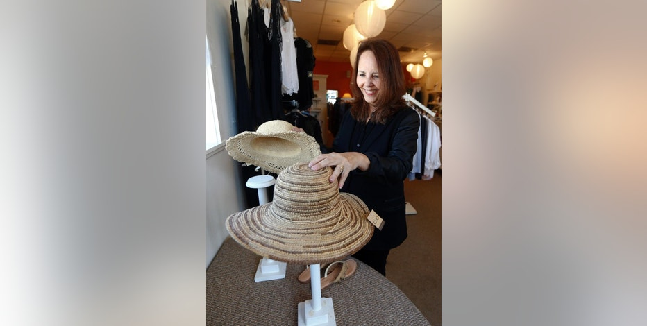 In this April 24, 2015 photo, Razzle Dazzle dress shop owner Carol Avendano arranges merchandise at her store in the Buckhead section of Atlanta. Razzle Dazzle's revenue is down 65 percent from 2007. Avendano sees customers think carefully before spending. (AP Photo/John Bazemore)
