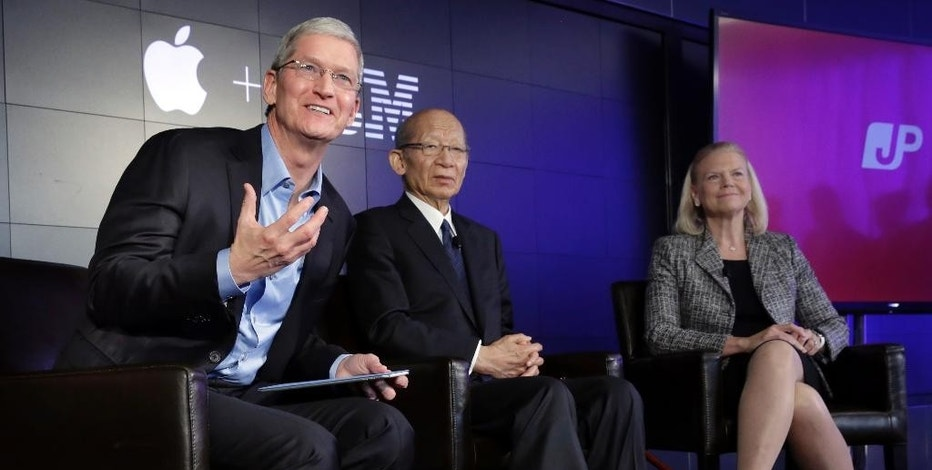 Apple CEO Tim Cook, left, addresses a news conference, joined by Japan Post CEO Taizo Nishimuro, and IBM CEO Ginni Rometty, at IBM Watson headquarters, in New York, Thursday, April 30, 2015. Apple, IBM and Japanese insurance and bank holding company Japan Post have formed a partnership to improve the lives of elderly people in the country. The program will provide iPads with apps designed to help seniors manage day-to-day lives and keep in touch with family members. (AP Photo/Richard Drew)