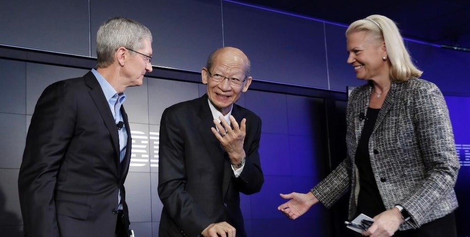 Apple CEO Tim Cook, Japan Post CEO Taizo Nishimuro, and IBM CEO Ginni Rometty, left to right, get together after a news conference at IBM Watson headquarters, in New York, Thursday, April 30, 2015. Apple, IBM and Japanese insurance and bank holding company Japan Post have formed a partnership to improve the lives of elderly people in the country. The program will provide iPads with apps designed to help seniors manage day-to-day lives and keep in touch with family members. (AP Photo/Richard Drew)