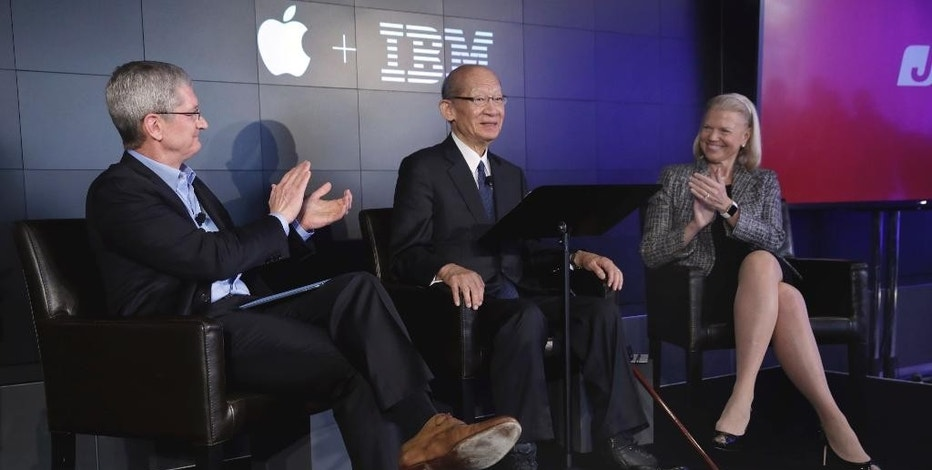 Apple CEO Tim Cook, left, and IBM CEO Ginni Rometty applaud as Japan Post CEO Taizo Nishimuro is introduced a news conference, at IBM Watson headquarters, in New York, Thursday, April 30, 2015. Apple, IBM and Japanese insurance and bank holding company Japan Post have formed a partnership to improve the lives of elderly people in the country. The program will provide iPads with apps designed to help seniors manage day-to-day lives and keep in touch with family members. (AP Photo/Richard Drew)