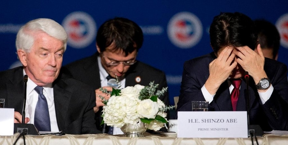 Japanese Prime Minister Shinzo Abe, right, with U.S. Chamber of Commerce president and CEO Tom Donohue, left, pauses during a meeting at the U.S. Chamber of Commerce in Washington, Wednesday, April 29, 2015. (AP Photo/Carolyn Kaster)