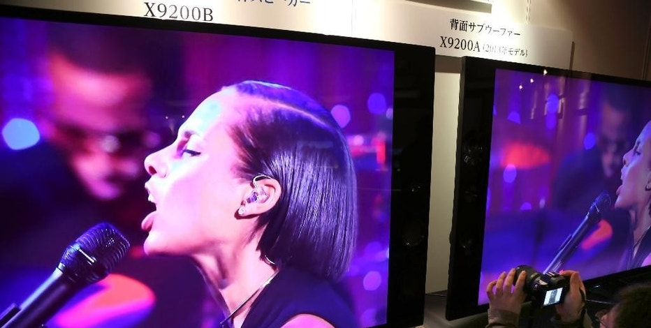 "FILE - In this April 15, 2014 file photo, a reporter takes photos of a Sony's ""Bravia"" 4K TV during an event unveiling new 4K products in Tokyo. Once at the leading edge of consumer electronics, Sony Corp. is now more lumbering giant than trend-setter after falling behind competitors such as Samsung Electronics Co. and Apple Inc. Sony watchers are urging the down-on-its-luck company to rediscover its pioneering ethos. (AP Photo/Koji Sasahara, File)"