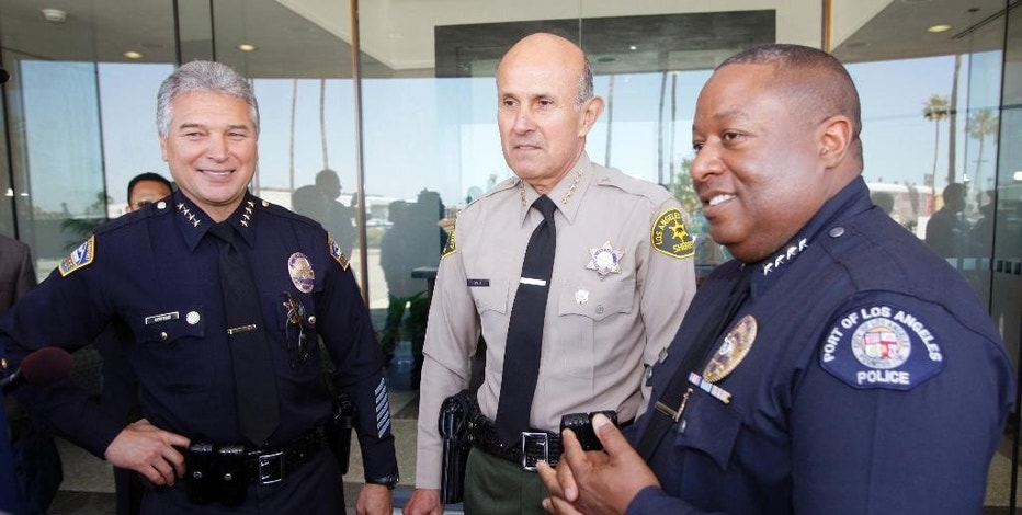 FILE - This April 25, 2011, file photo shows, from left, Los Angeles Airport Police Chief George Centeno, Los Angeles County Sheriff Lee Baca and Los Angeles Port Police Chief Ronald Boyd at the opening of the Port of Los Angeles Maritime Law Enforcement Training Center in Los Angeles. Boyd was charged Thursday, April 30, 2015, in an alleged kickback and bribery scheme involving a social networking program that was supposed to help reduce port crime. Boyd was named in a 16-count federal grand jury indictment that alleged wire fraud, lying to FBI agents, tax evasion and failing to file federal corporate tax returns. Boyd remains on the job and agreed to surrender to federal agents next week. (AP Photo/Damian Dovarganes, File)