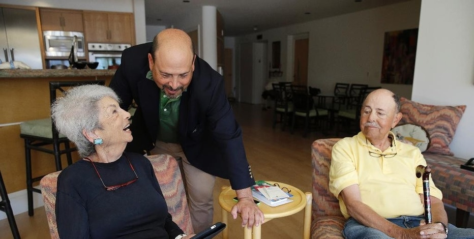 In this March 17, 2015 photo, Phil Dworsky visits with his parents, Dorothy and Bill Dworsky, at their home in San Francisco. Each time an elder Dworksy opens the refrigerator, closes the bathroom door or lifts the lid on a pill container, tiny sensors in their home make notes on a digital logbook, which the younger Dworsky monitors daily on his smartphone. (AP Photo/Eric Risberg)