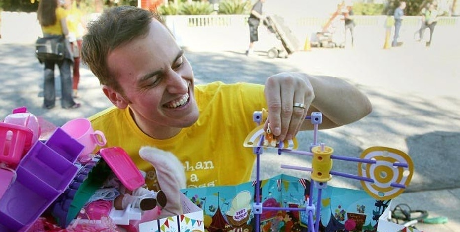 Beau Lewis, GoldieBlox chief marketing officer, puts together a Goldie Blox's Spinning Machine toy set, in Pasadena, Calif., before a film crew films a commercial for his company.