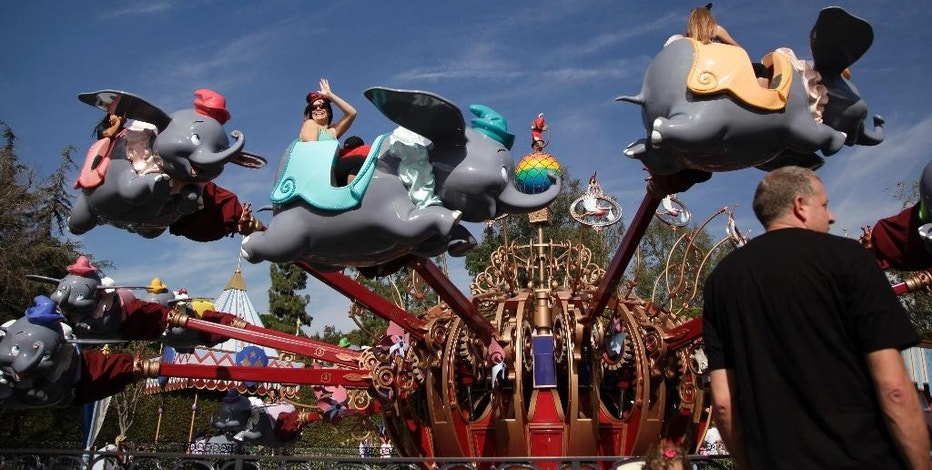 FILE - In this Jan. 22, 2015 file photo, visitors ride the Dumbo the Flying Elephant ride at Disneyland in Anaheim, Calif. Disney reports quarterly financial results Tuesday, May 5, 2015. (AP Photo/Jae C. Hong, File)