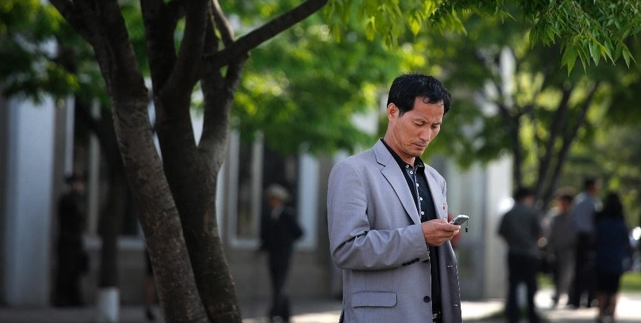 In this Tuesday, May 5, 2015, photo, a man uses his mobile phone in Pyongyang, North Korea. North Korean officials have unveiled a mobile-friendly online shopping site. (AP Photo/Wong Maye-E)