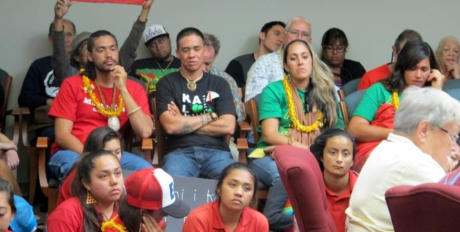 "FILE - In this April 30, 2015 file photo, People crowd into an Office of Hawaiian Affairs boardroom in Honolulu for a meeting about building the Thirty Meter Telescope near the summit of Mauna Kea, which many Native Hawaiians consider sacred. Some opponents of the construction of one of the world's largest telescopes describe fighting the telescope as an ""awakening,"" an issue Native Hawaiians can band together against. But their reasons vary, from preventing Mauna Kea's desecration to preserving culture to curbing development. (AP Photo/Jennifer Sinco Kelleher, File)"