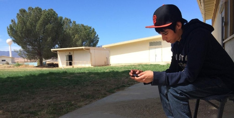 In this April 30, 2015 photo, Brian Olivas, 17, looks at his smartphone between classes at the Cuyama Valley High School in New Cuyama, Calif. The Cuyama Joint Unified School District is 60 miles from the nearest city and has Internet connections about one-tenth the minimum speed recommended for the modern U.S. classroom. Across the country, school districts in rural areas and other pockets with low bandwidth are confronting a difficult task of administering new Common Core-aligned standardized tests to students online. (AP Photo/Christine Armario)