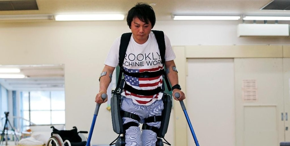In this April 17, 2015 photo, Yuichi Imahata walks using a robotic exoskeleton called ReWalk at Kanagawa Rehabilitation Center in Atgugi, west of Tokyo. Imahata, 31, has been using a wheelchair to get around for seven years after a serious spinal-cord injury suffered in an accidental fall while working for a transport company. He completely lost sensation in both his legs and was told he would never walk again. (AP Photo/Shuji Kajiyama)