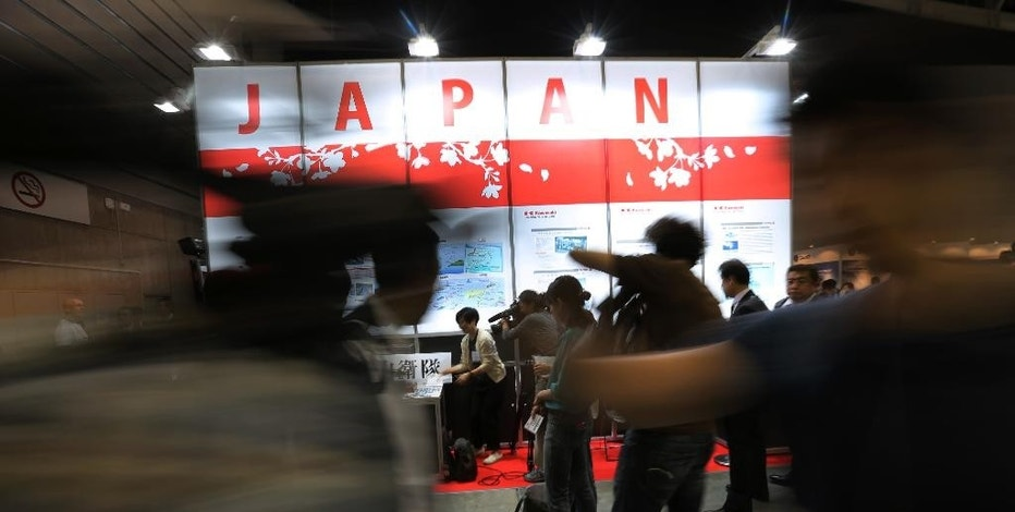 Visitors walk by a section of Japanese companies at a first-ever defense industry fair in Yokohama, Wednesday, May 13, 2015. A year after Japan eased a longstanding ban on military exports, barely a trickle of deals has formed for its powerhouse manufacturers who are reckoning with latecomer status in a crowded global industry. (AP Photo/Eugene Hoshiko)