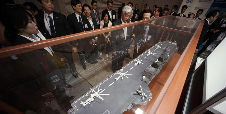 Japanese Defense Minister Gen Nakatani, center, looks at a scale model of Izumo-class helicopter destroyer at a first-ever defense industry fair in Yokohama, south of Tokyo, Wednesday, May 13, 2015. A year after Japan eased a longstanding ban on military exports, barely a trickle of deals has formed for its powerhouse manufacturers who are reckoning with latecomer status in a crowded global industry. (AP Photo/Eugene Hoshiko)