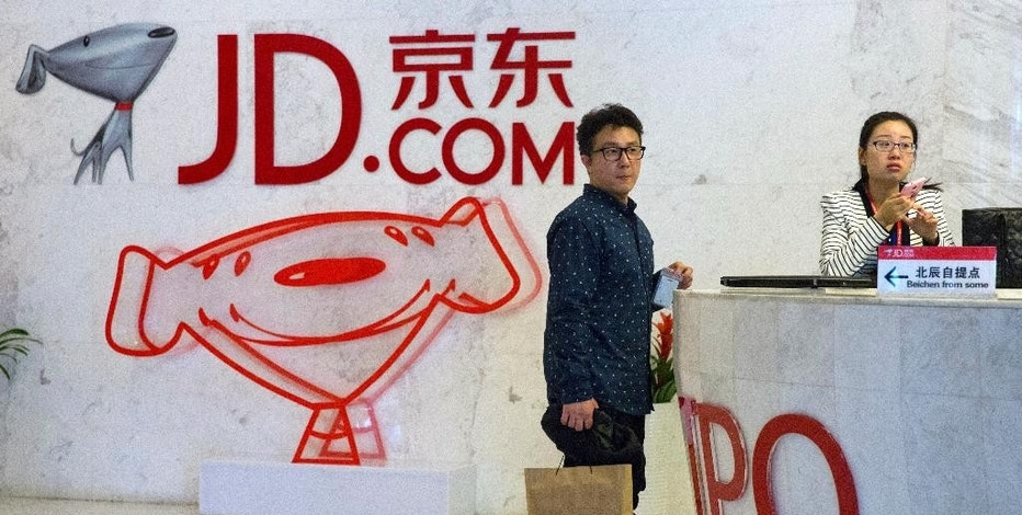 In this photo taken April 2, 2015, visitors wait at the entrance to JD.com head office in Beijing. Since it went online in 2003, JD.com has grown into China's biggest Internet-based direct retailer. It is a powerful selling point for Chinese consumers who have endured repeated scandals over fake and sometimes deadly milk, medicines and other products. (AP Photo/Ng Han Guan)
