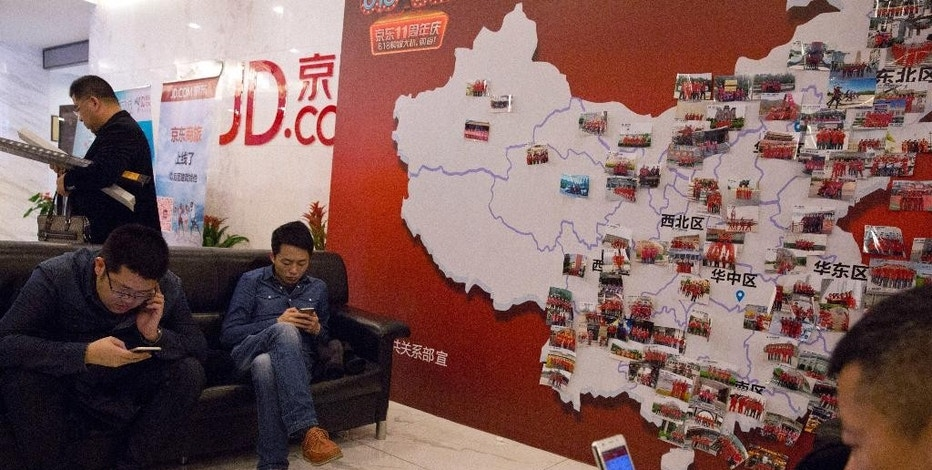 In this photo taken April 2, 2015, visitors wait at the entrance to JD.com head office near a board displaying the company's staff around the country in Beijing. Since it went online in 2003, JD.com has grown into China's biggest Internet-based direct retailer. It is a powerful selling point for Chinese consumers who have endured repeated scandals over fake and sometimes deadly milk, medicines and other products. (AP Photo/Ng Han Guan)