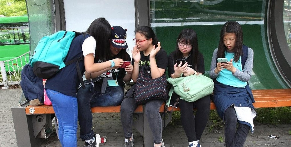 """South Korean middle school students use their smartphones at a bus station in Seoul, South Korea, Friday, May 15, 2015. The app, """"Smart Sheriff,"""" was funded by the South Korean government primarily to block access to pornography and other offensive content online. But its features go well beyond that. Smart Sheriff and at least 14 other apps allow parents to monitor how long their kids use their smartphones, how many times they use apps and which websites they visit. Some send a child's location data to parents and issue an alert when a child searches keywords such as """"suicide,"""" ''pregnancy"""" and """"bully"""" or receives messages with those words. (AP Photo/Ahn Young-joon)"""