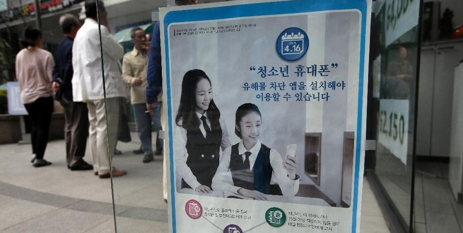 """A promotional banner of mobile apps that block harmful contents, is posted on the door at a mobile store in Seoul, South Korea, Friday, May 15, 2015. The banner reads: """"Young smartphone users, you must install apps that block harmful content."""" """"Smart Sheriff"""" app was funded by the South Korean government primarily to block access to pornography and other offensive content online. But its features go well beyond that. Smart Sheriff and at least 14 other apps allow parents to monitor how long their kids use their smartphones, how many times they use apps and which websites they visit. Some send a child's location data to parents and issue an alert when a child searches keywords such as """"suicide,"""" ''pregnancy"""" and """"bully"""" or receives messages with those words. (AP Photo/Lee Jin-man)"""