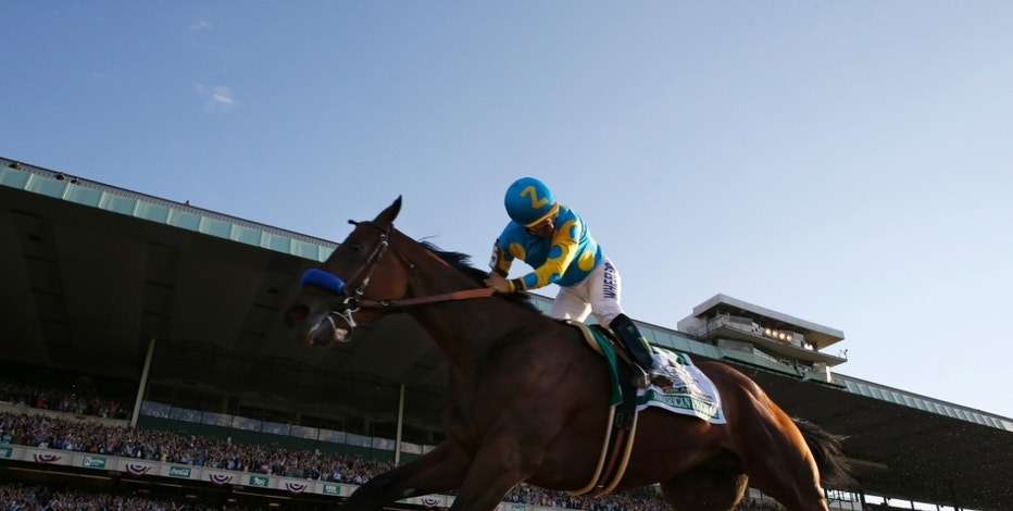 Victor Espinoza looks back after crossing the finish line with American Pharoah to win the 147th running of the Belmont Stakes horse race at Belmont Park, Saturday, June 6, 2015, in Elmont, N.Y. (AP Photo/Julio Cortez)