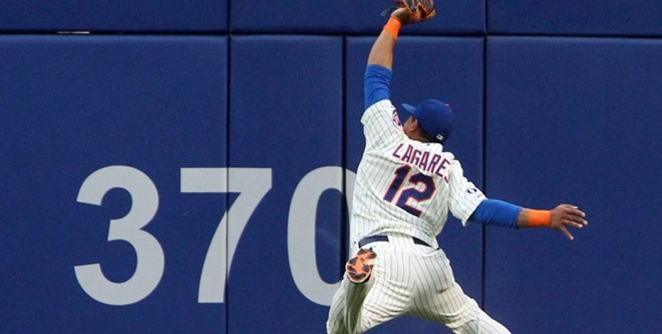 New York Mets center fielder Juan Lagares (12) catches a ball hit by San Francisco Giants first baseman Brandon Belt in the second inning at Citi Field, Aug. 2, 2014.
