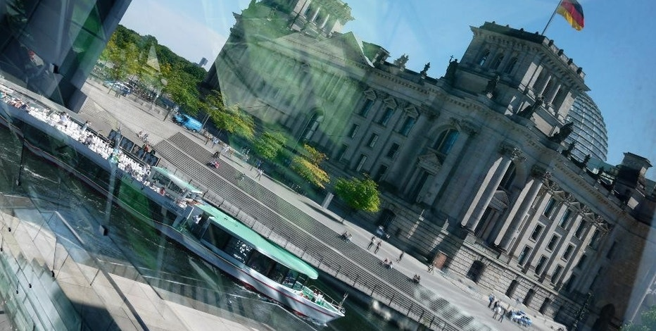 A ship passes by the Reichstag building which is reflected in the windows of another building of the German parliamentary complex in Berlin, Thursday, June 11, 2015. German lawmakers are mulling whether to replace their entire computer system after a sophisticated hacking attack against the Parliament's IT network. (AP Photo/Ferdinand Ostrop)
