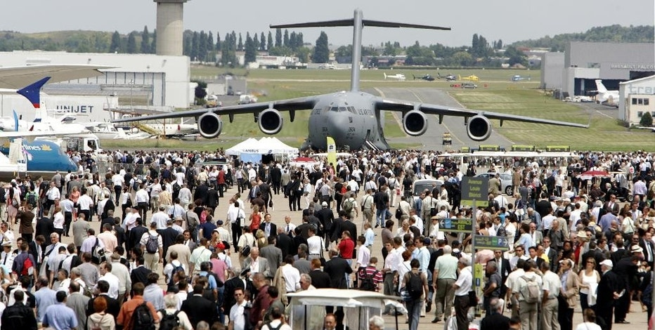 FILE - This June 17, 2009 file photo shows a US Air Force Boeing-made Globe Master III  in background as visitors crowd the tarmac, at Le Bourget, north of Paris, during the 48th Paris Air Show. Just eight miles from the center of Paris, the normally sleepy aerodrome in Le Bourget will undergo its biennial transformation into the center of the world's $700 billion aerospace and defense industry when it hosts the 51st International Paris Air Show from June 15 to June 21. (AP Photo/Remy de la Mauviniere/File)