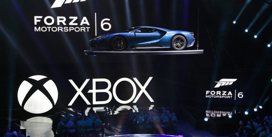 """A Ford GT ultra-high-performance supercar, the cover car in the next iteration of the racing simulation franchise for Xbox, """"Forza Motorsport 6,"""" is lowered to the stage at the Xbox E3 2015 briefing ahead of the Electronic Entertainment Expo at the University of Southern California's Galen Center on Monday, June 15, 2015 in Los Angeles. (AP Photo/Damian Dovarganes)"""