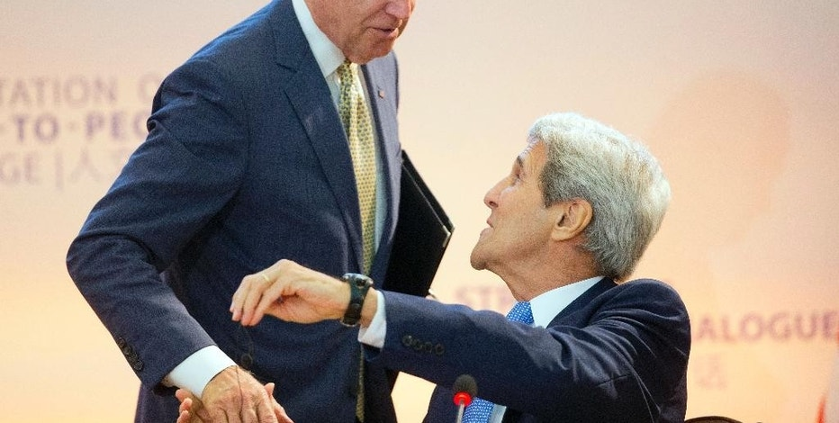 Vice President Joe Biden, left, shakes hands with Secretary of State John Kerry, right seated, after speaking at the 7th US China Strategic and Economic Dialogue  (S&ED) and 6th Consultation on People-to-People (CPE) at the US State Department in Washington, Tuesday, June 23, 2015.(AP Photo/Pablo Martinez Monsivais)