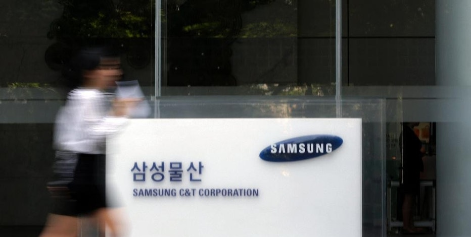 In this photo taken on May 26, 2015, an office worker walks by a logo of Samsung C&T Corp. at its head office in Seoul, South Korea. Thousands of South Korean investors are backing an American hedge fund's bid to thwart a business combination between Samsung companies that they argue will only enrich the conglomerate's wealthy founding family. (AP Photo/Lee Jin-man)