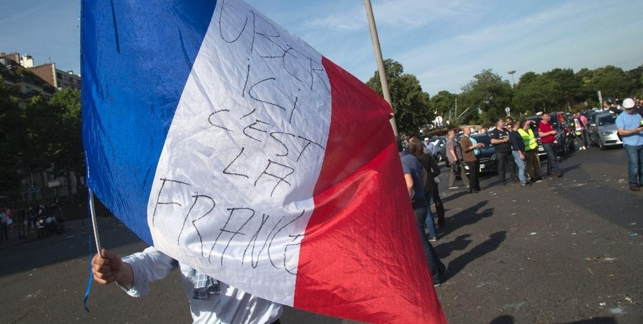 "A taxi driver waves a French flag with inscription reading ""Uber, here it's  France"" during a demonstration in Paris, Thursday, June 25, 2015 in Paris. French taxis are on strike around the country, snarling traffic in major cities and slowing access to Paris' Charles de Gaulle airport after weeks of rising and sometimes violent tensions over Uber. (AP Photo/Michel Euler)"