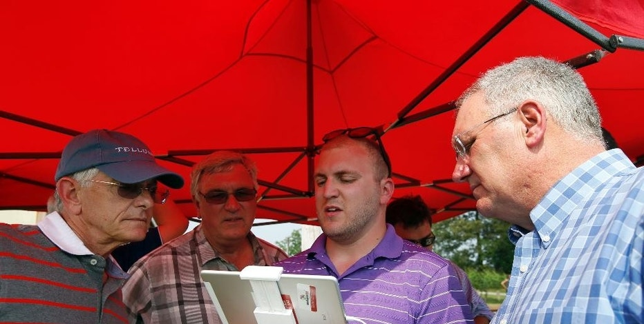 In this June 11, 2015 photo, Mike Geske, left, from Sikeston, Mo., Bob Bowman, from DeWitt, Iowa, with Kevin Skunes, right, from Arthur, N.D., watch the display as Matthew Creger, left, marketing director for Intelligent UAS, during a drone demonstration at a farm and winery on potential use for board members of the National Corn Growers in Cordova, Md. The small, relatively inexpensive unmanned aerial vehicles could replace humans in a variety of ways around large farms, transmitting detailed information about crops, directing farmers to problem spots and cutting down on the amount of water and chemicals used. (AP Photo/Alex Brandon)