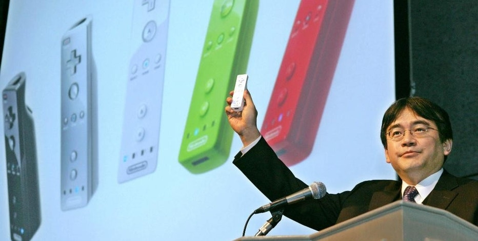FILE - In this Sept. 16, 2005 file photo, Nintendo Co. Ltd. President Satoru Iwata displays a new smaller remote control device as he makes a key cameo appearance at the annual Tokyo Game Show in Makuhari, east of Tokyo.  Nintendo said President Iwata died Saturday, July 11, 2015, of a bile duct tumor in a Kyoto hospital, western Japan.   (AP Photo/Koji Sasahara, File)