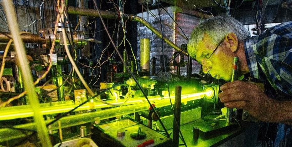 In this Monday, June  8, 2015 photo, scientist Anatoly Bonert tends to a magnesium atomic clock in Novosibirsk, Russia. Hundreds of Russian scientists are reporting experiences of being refused sale of scientific equipment from abroad, or seeing research papers turned down by Western publications. The reason, they believe, is a combination of sanctions against Russia over its actions in Ukraine and rising hostility to Russia in the West seeping into the scientific community. (AP Photo/Alexander Lukin)