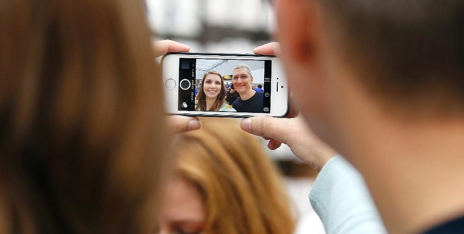 FILE - In this Sept. 19, 2014 file photo, Apple CEO Tim Cook, right, takes a photo with an Apple employee during the launch and sale of the new iPhone 6 at an Apple store in Palo Alto, Calif. Analysts expect the California tech giant's quarterly financial report Tuesday, July 21, 2015, will show another powerhouse performance. Apple's signature iPhones remain popular, even as other smartphone makers are seeing demand slow down. (AP Photo/Tony Avelar, File)