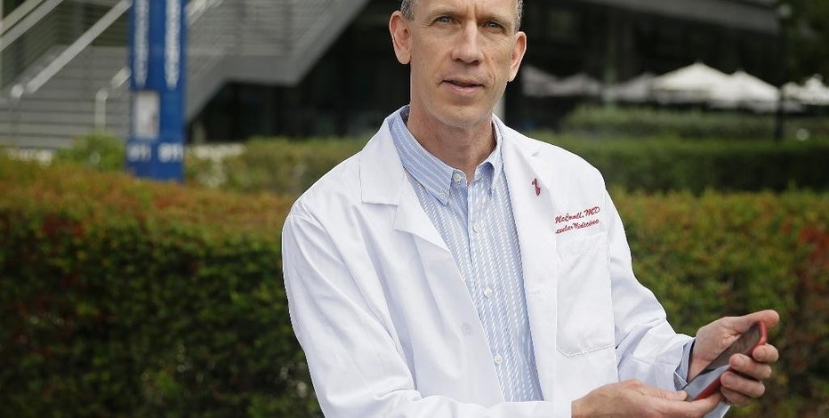 In this photo taken Tuesday, July 7, 2015, Dr. Michael V. McConnell, a cardiologist who's using an app to study heart disease, poses with his smartphone outside the Stanford Medical School in Stanford, Calif. Scientists like McConnell who are overseeing studies that use specialized iPhone apps say they have the potential to transform medical research by helping them collect data routinely from far more people than usually participate in health studies. (AP Photo/Eric Risberg)