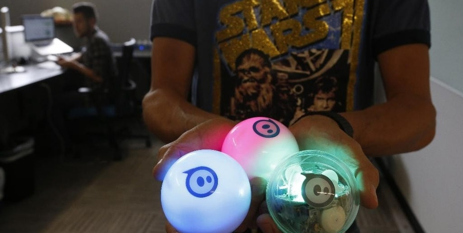 "In this July 24, 2015 photo, examples of the remote controlled ball toy called Sphero sit are held by an employee at Sphero, a fast-growing toy robotics company in Boulder, Colo. The company has collaborated with Lucasfilm-parent Disney to develop the BB-8, a droid character which will be featured in ""Star Wars: Episode VII - The Force Awakens."" (AP Photo/Brennan Linsley)"
