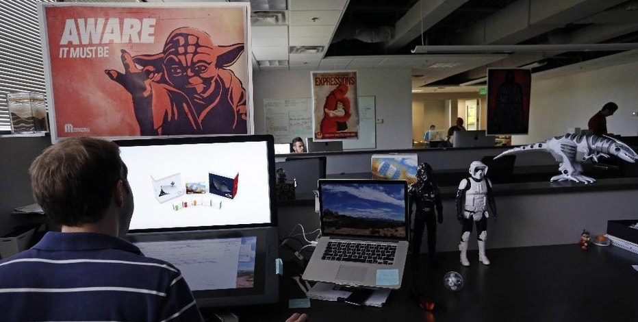 "In this July 24, 2015 photo, an employee at Sphero, a fast-growing toy robotics company, works surrounded by Star Wars toys and posters, at the company headquarters in Boulder, Colo. The company has collaborated with Lucasfilm-parent Disney to develop the BB-8, a droid character which will be featured in ""Star Wars: Episode VII - The Force Awakens."" (AP Photo/Brennan Linsley)"