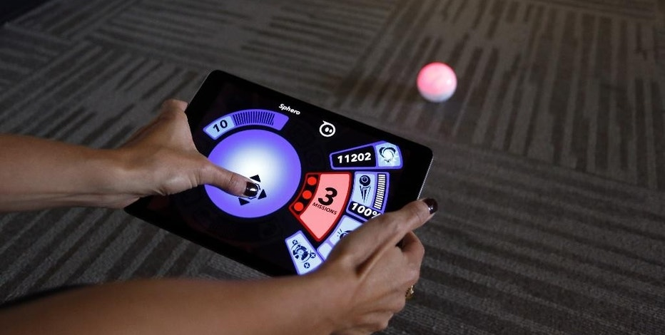 "In this July 24, 2015 photo, an employee at Sphero, a fast-growing toy robotics company, plays with the remote controlled Sphero toy, at the company's headquarters in Boulder, Colo. The company has collaborated with Lucasfilm-parent Disney to develop the BB-8, a droid character which will be featured in ""Star Wars: Episode VII - The Force Awakens."" (AP Photo/Brennan Linsley)"