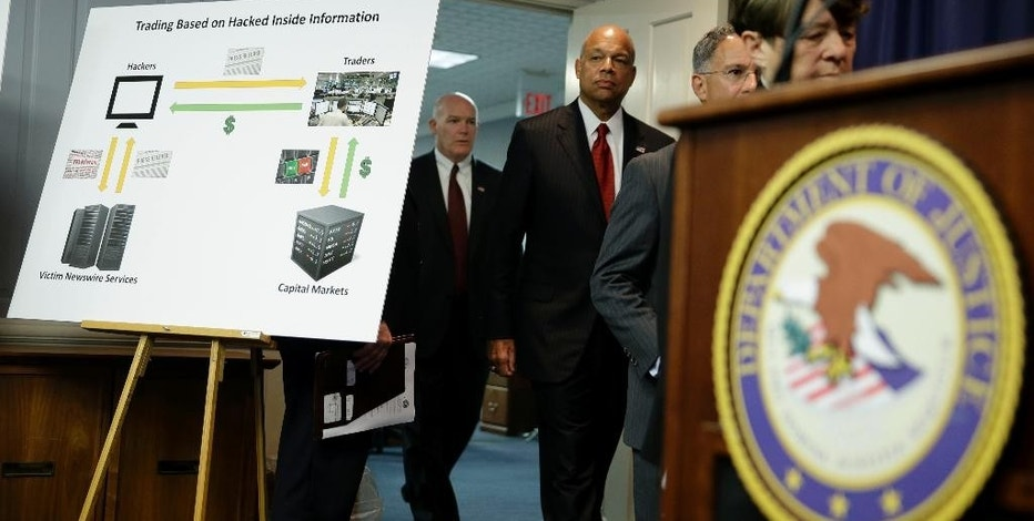 A poster board detailing an insider trading scam involving hacking is displayed at the start of a news conference in Newark, N.J., Tuesday, Aug. 11, 2015. An international group of hackers and stock traders made $30 million by breaking into the computers of newswire services that put out corporate press releases and trading on the information before it was made public, federal prosecutors said Tuesday. (AP Photo/Seth Wenig)