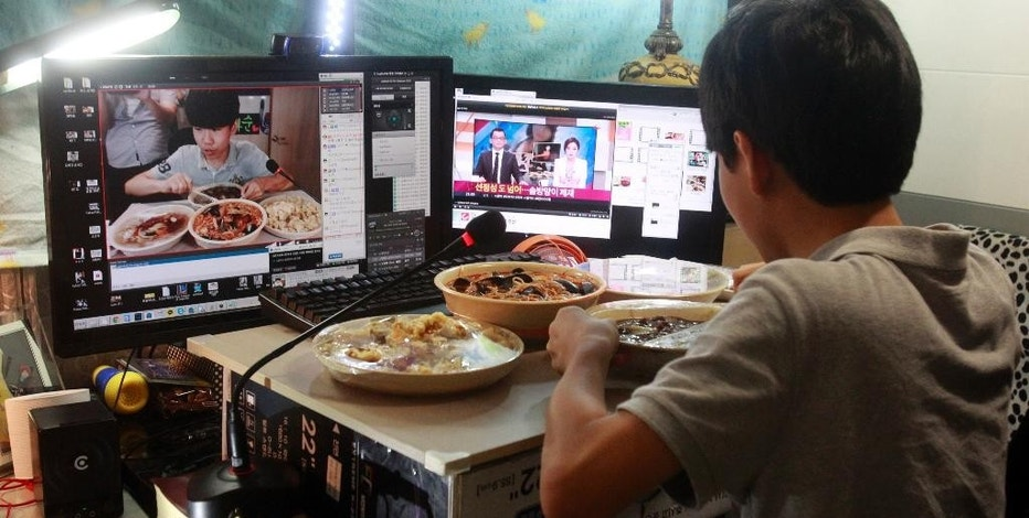 In this Monday, Aug. 17, 2015 photo, Kim Sung-jin, 14, broadcasts himself eating delivery Chinese food in his room at home in Bucheon, south of Seoul, South Korea. Every evening, he gorges on food as he chats before a live camera with hundreds, sometimes thousands, of teenagers watching. That's the show, and it makes Kim money: 2 million won ($1,700) in his most successful episode. Better known to his viewers by the nickname Patoo, he is one of the youngest broadcasters on Afreeca TV, an app for live-broadcasting video online launched in 2006. (AP Photo/Julie Yoon)