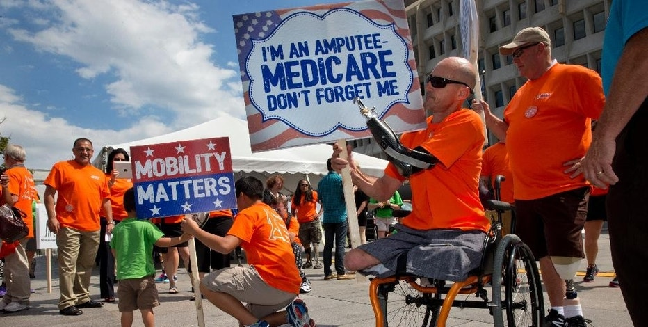 Billy Kidwell, of Bivalve, Md., right, who is a triple amputee, attends a protest with the Amputee Coalition against a Medicare change in payment policy for lower limb prosthetics including artificial feet, in Washington, Wednesday, Aug. 26, 2015. (AP Photo/Jacquelyn Martin)