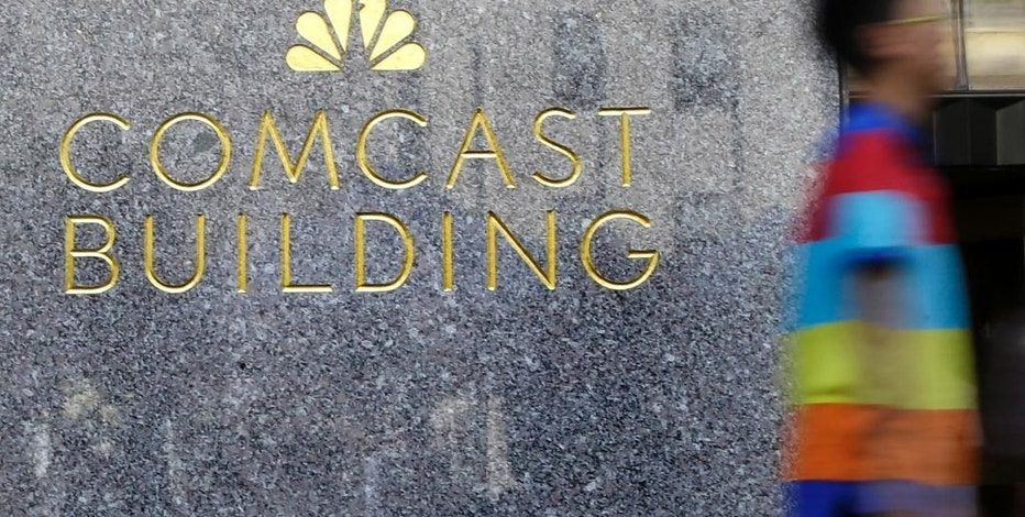 In this July 23, 2015 photo, a man walks past the Comcast Building in New York. Comcast, which became a TV powerhouse by signing up Generation Xers, baby boomers and their parents, now is fighting for millennial eyeballs. (AP Photo/Mary Altaffer)
