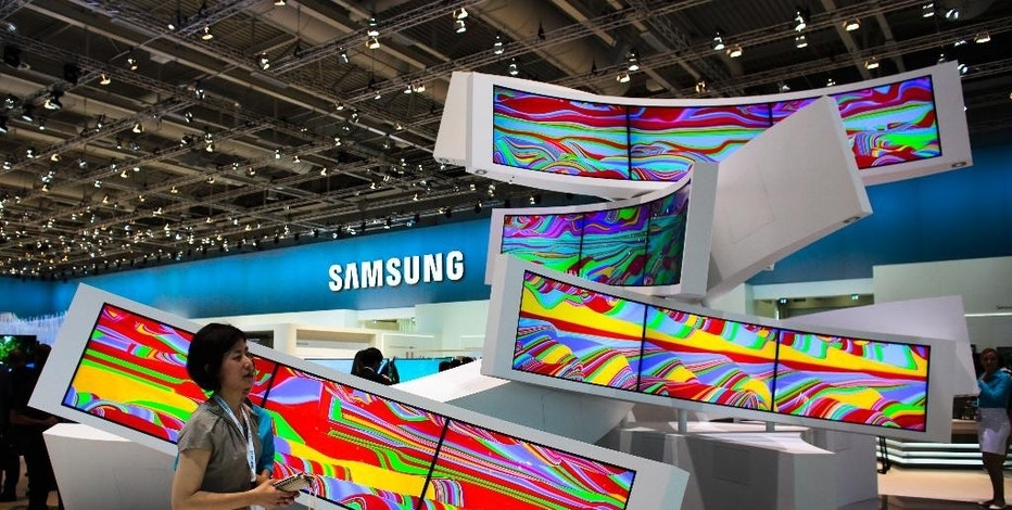 FILE - This is a Friday, Sept. 5, 2014 file photo of a woman as she passes an installation with curved screens, displayed by Samsung at the consumer electronic fair IFA in Berlin, Germany. Europe's flagship gadget show, the IFA in Berlin, opens its doors to the public on Friday Sept. 4, 2015 . Almost 1,500 companies and over 250 000 people are expected to visit the event, which runs through Sept. 9. (AP Photo/Markus Schreiber)