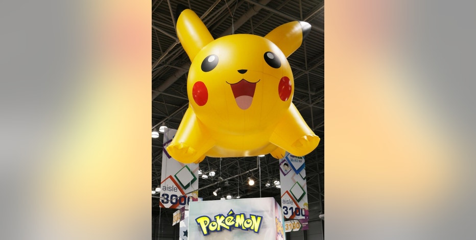 "FILE - In this Feb. 16, 2014 file photo, a Pikachu of Pokemon display hangs above Toy Fair 2014 at the Jacob K. Javits Convention Center in New York on the opening day of the 111th American International Toy fair. Japanese video game company Nintendo Co., the Pokemon Co. and Google spin-off Niantic said Thursday, Sept. 10, 2015 they intend to transplant the virtual realities of the famous Pokemon ""pocket monsters"" into real world locations with a smartphone app that players can use to catch, trade and stage battles between the creatures. (AP Photo/Frank Franklin II, File)"