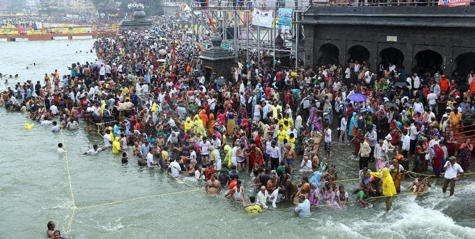 Hindu devotees gather for the third royal bath in the river Godavari during the ongoing Kumbh Mela, or Pitcher Festival, in Nashik, Maharashtra state, India, Friday, Sept. 18, 2015. Hindus believe taking a dip in the waters of a holy river during the festival will cleanse them of their sins. According to Hindu mythology, the Kumbh Mela celebrates the victory of gods over demons in a furious battle over a nectar that would give them immortality.(AP Photo/Ajaj Shaikh)
